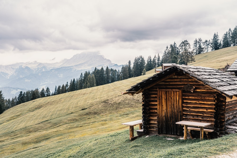 brown wooden house on green grass field near green trees and mountains during daytime