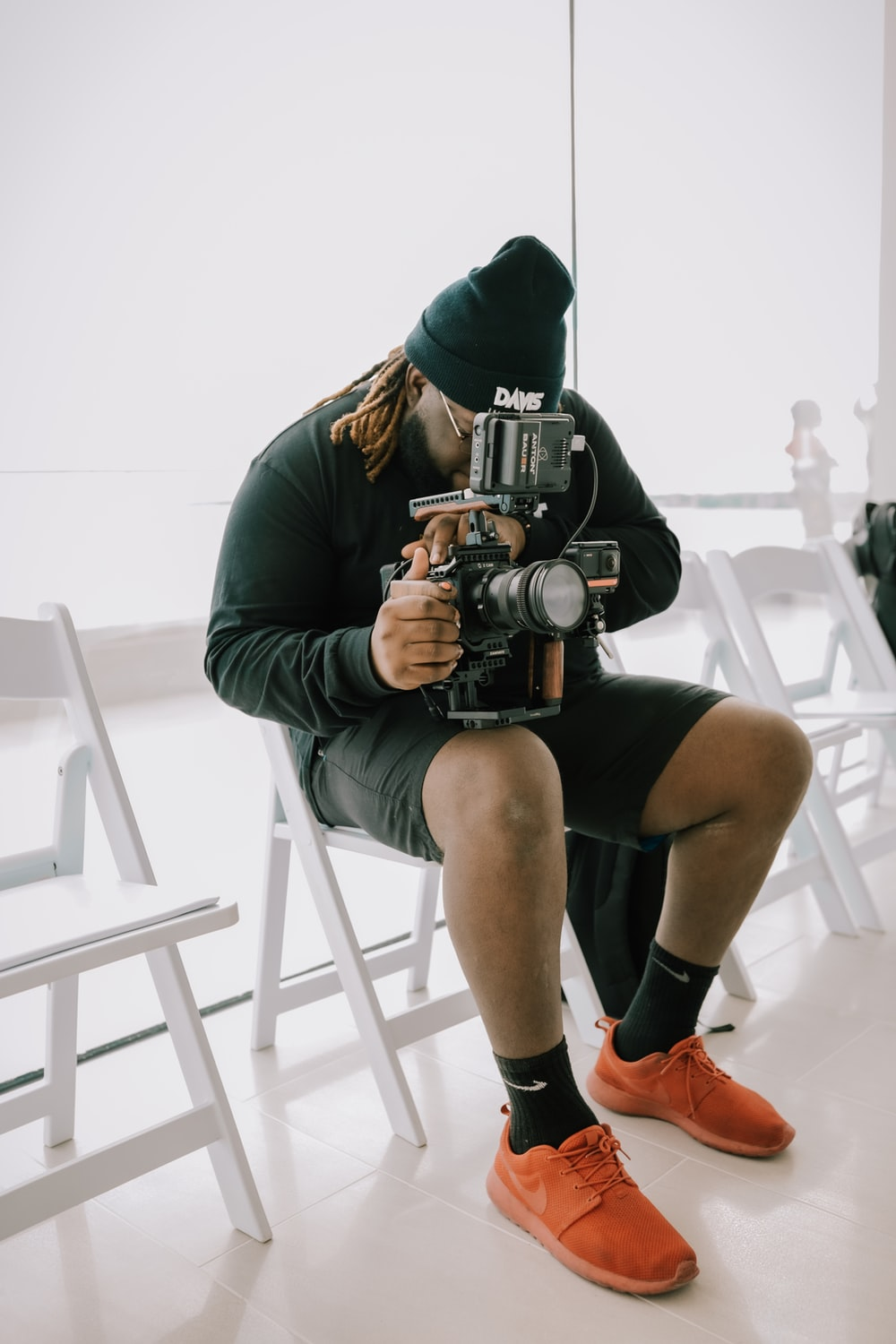 man in gray hoodie and black shorts sitting on white chair holding black dslr camera