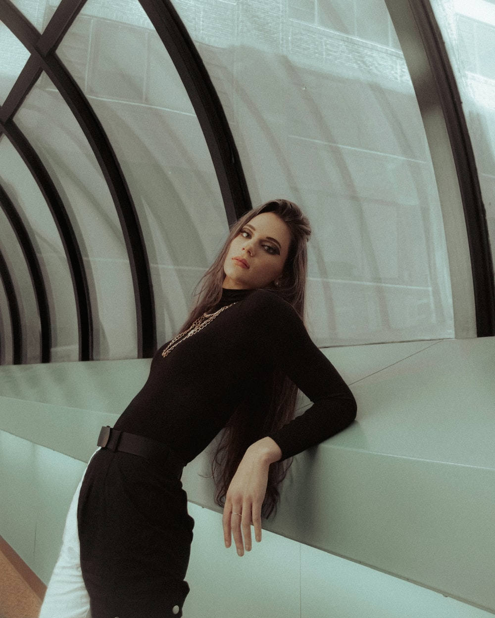 woman in black long sleeve shirt and black pants standing beside glass wall