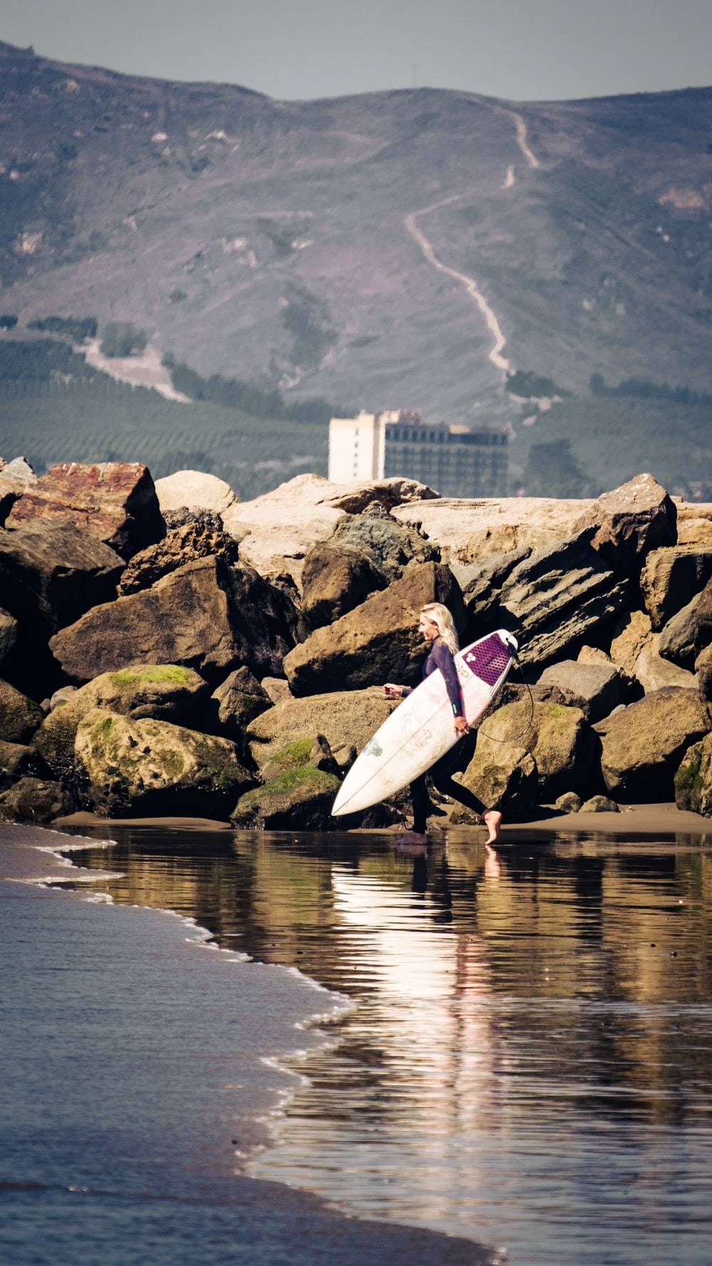 woman in pink long sleeve shirt and white pants holding white surfboard standing on rocky shore