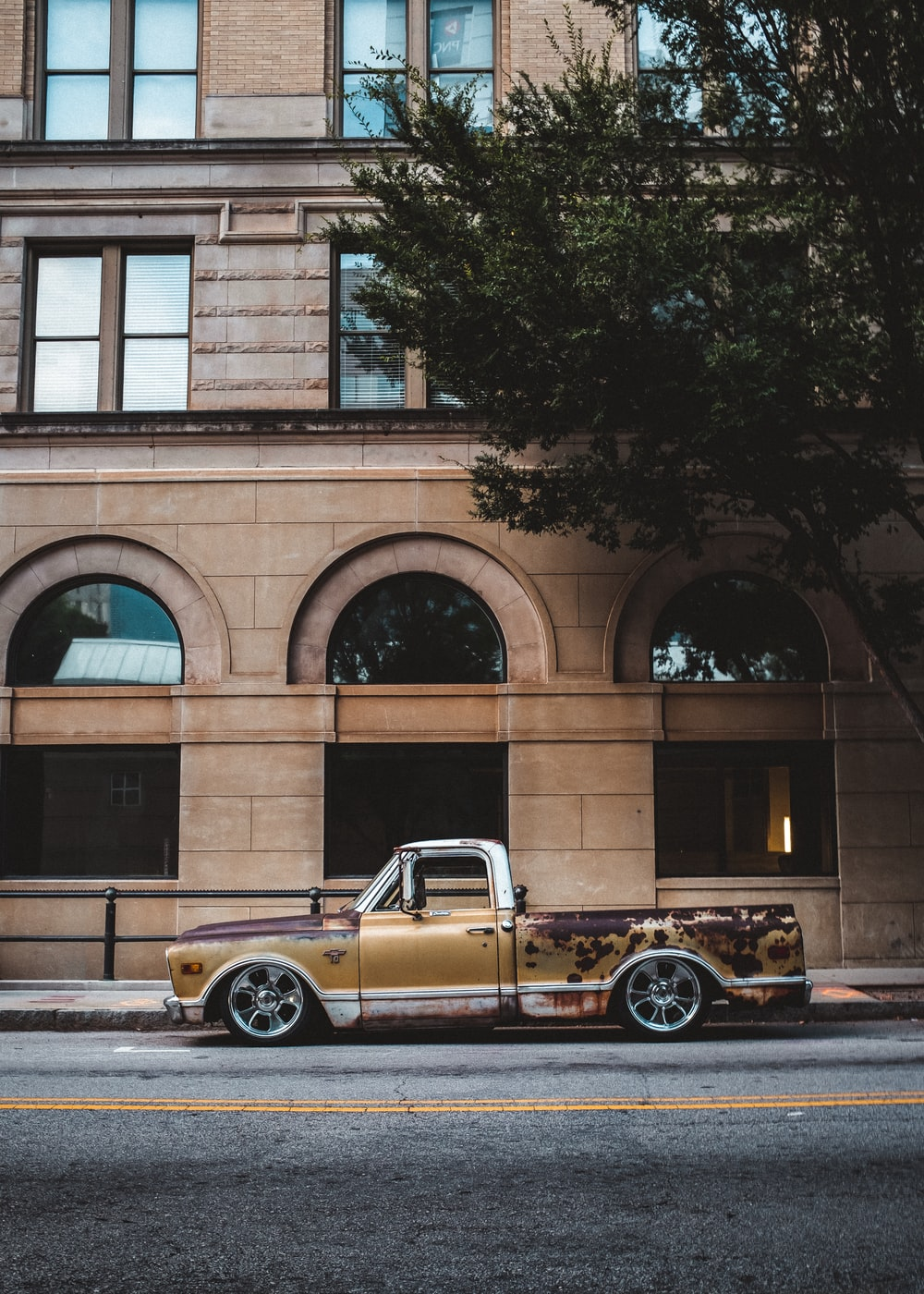 brown coupe parked beside brown concrete building during daytime