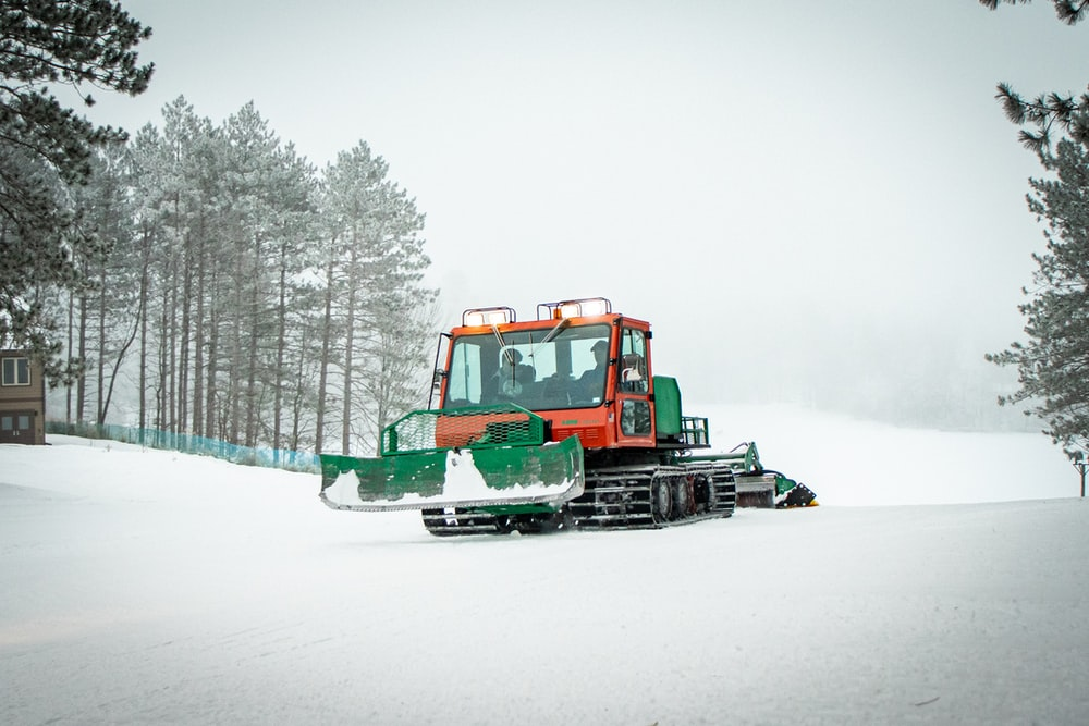 green and red heavy equipment on snow covered ground
