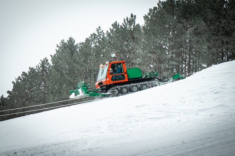 green and orange tractor on snow covered ground during daytime