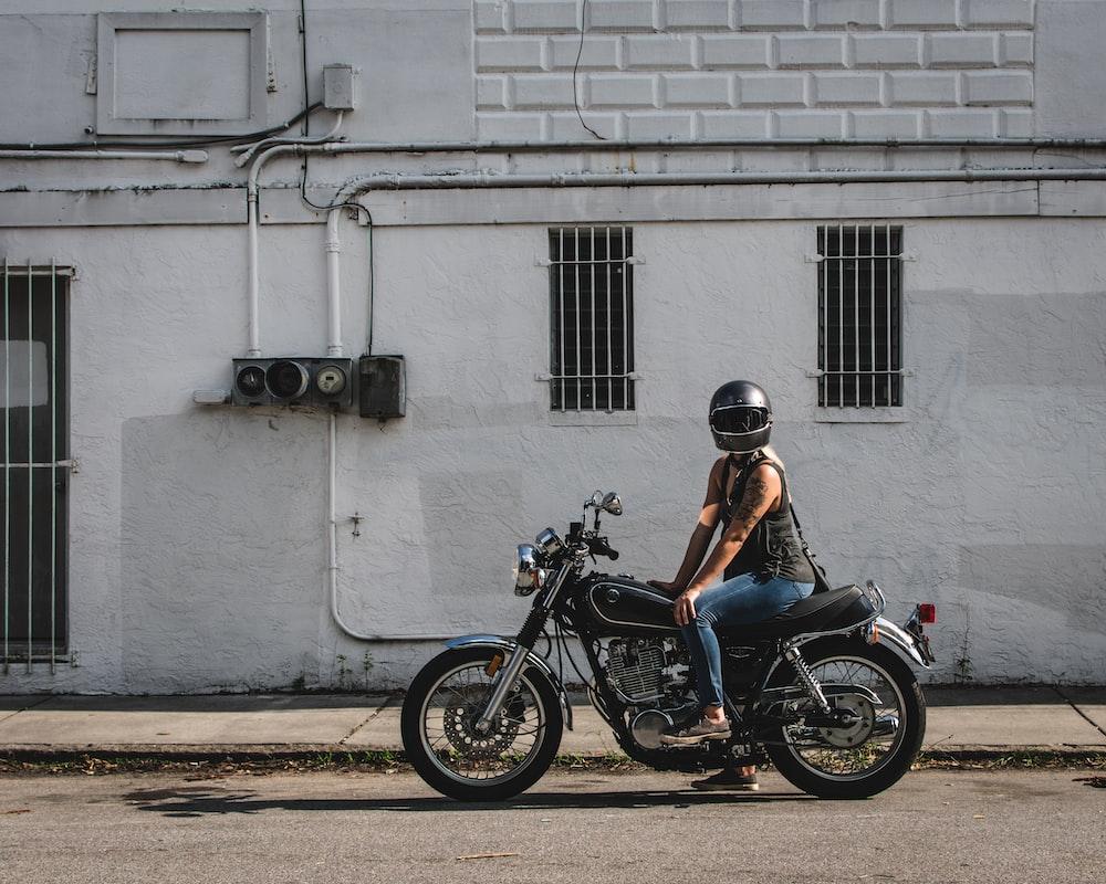 man in blue shirt riding black motorcycle