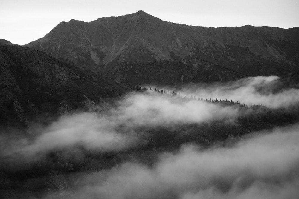 grayscale photo of mountains with fog