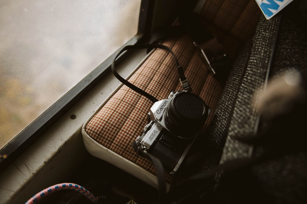 black and silver dslr camera on brown wooden table
