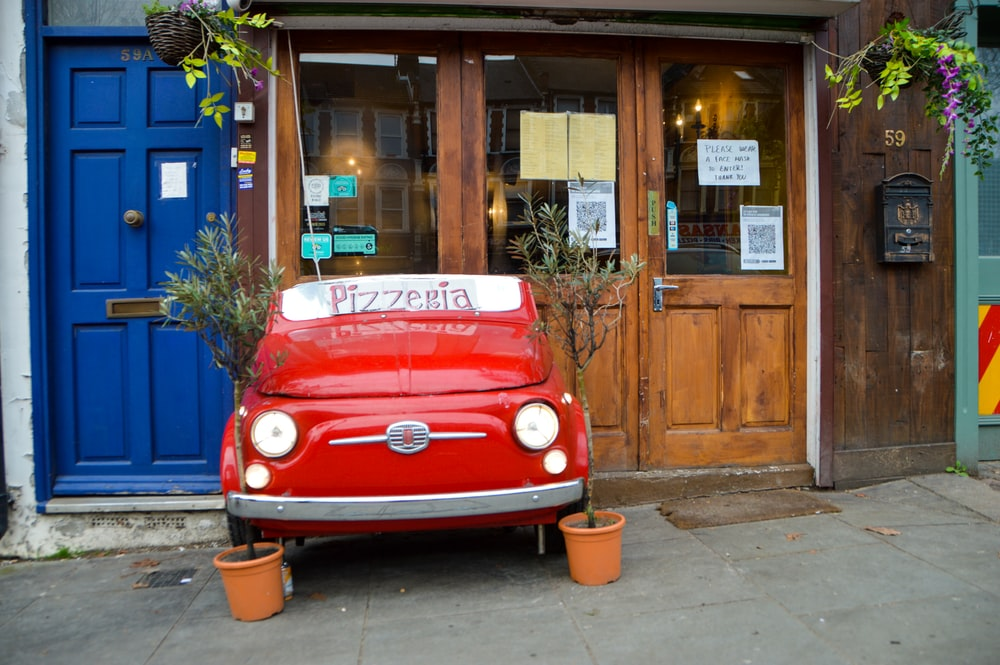 red volkswagen t-2 van parked beside brown wooden building during daytime