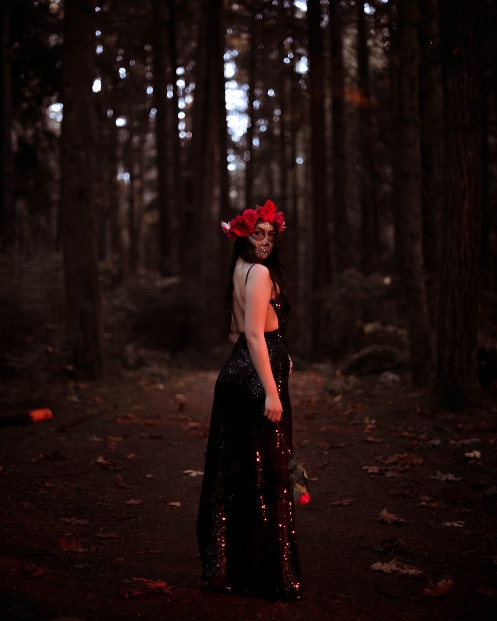 woman in black dress standing in the woods