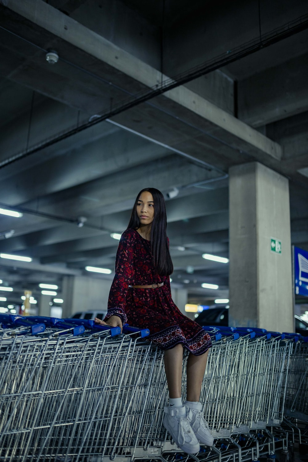 woman in red and black dress sitting on blue shopping cart