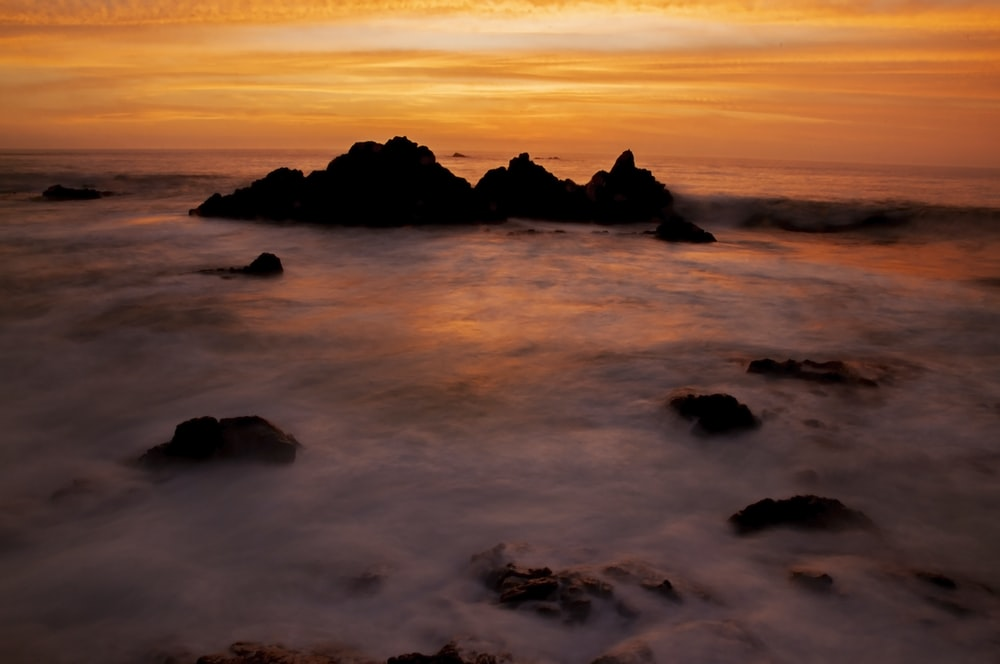 silhouette of rock formation on sea during sunset