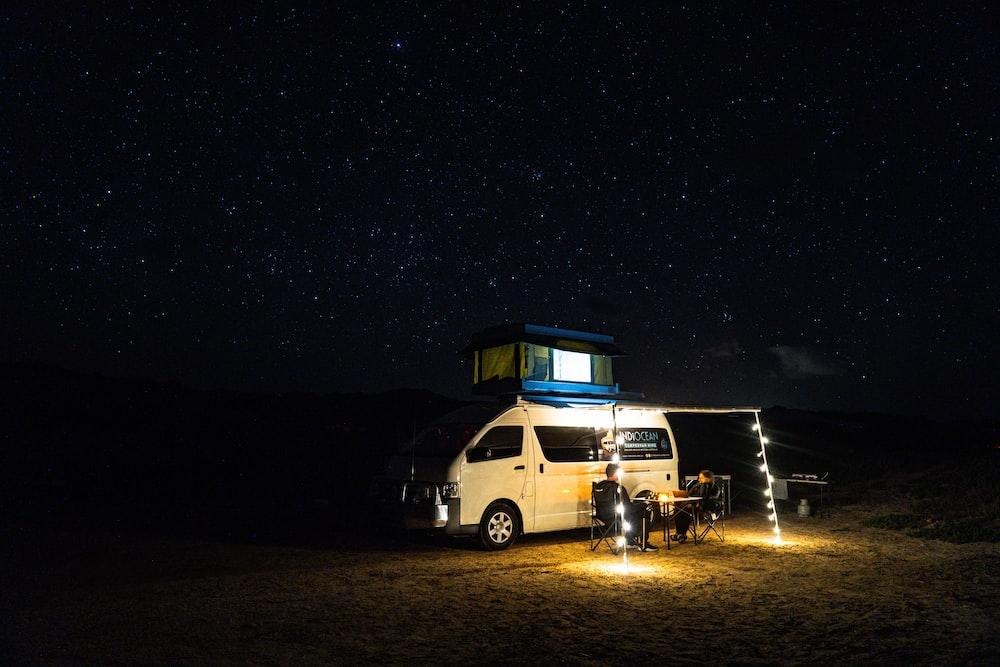 white van on brown sand during night time