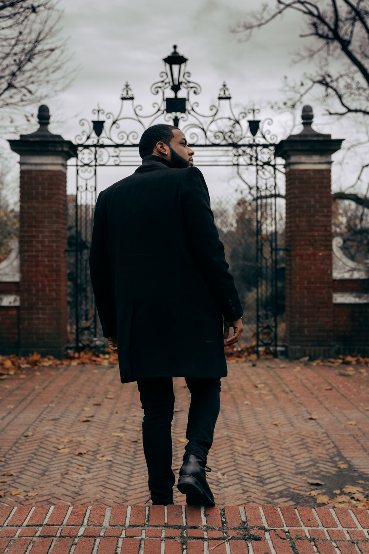 man in black coat standing on brick pavement