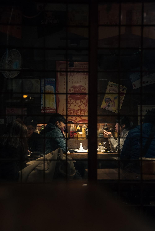 people sitting on chair near glass window
