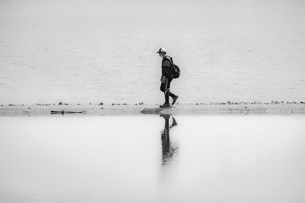 man in black jacket standing on snow covered ground during daytime