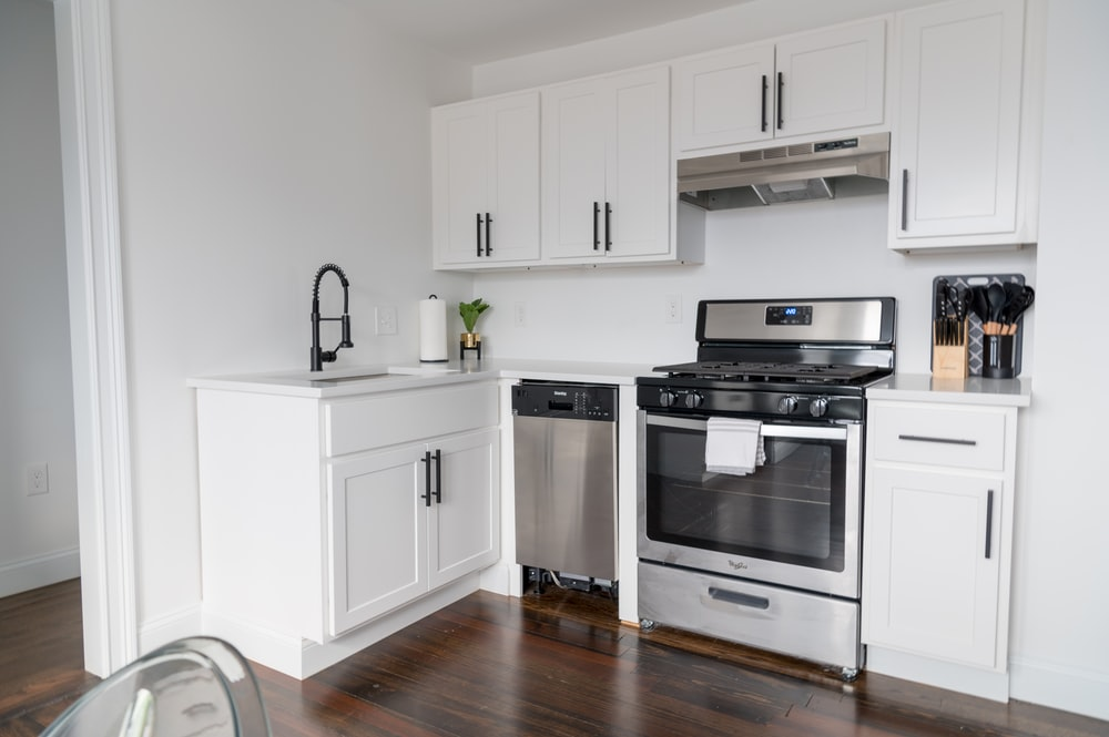 white wooden kitchen cabinet and white microwave oven