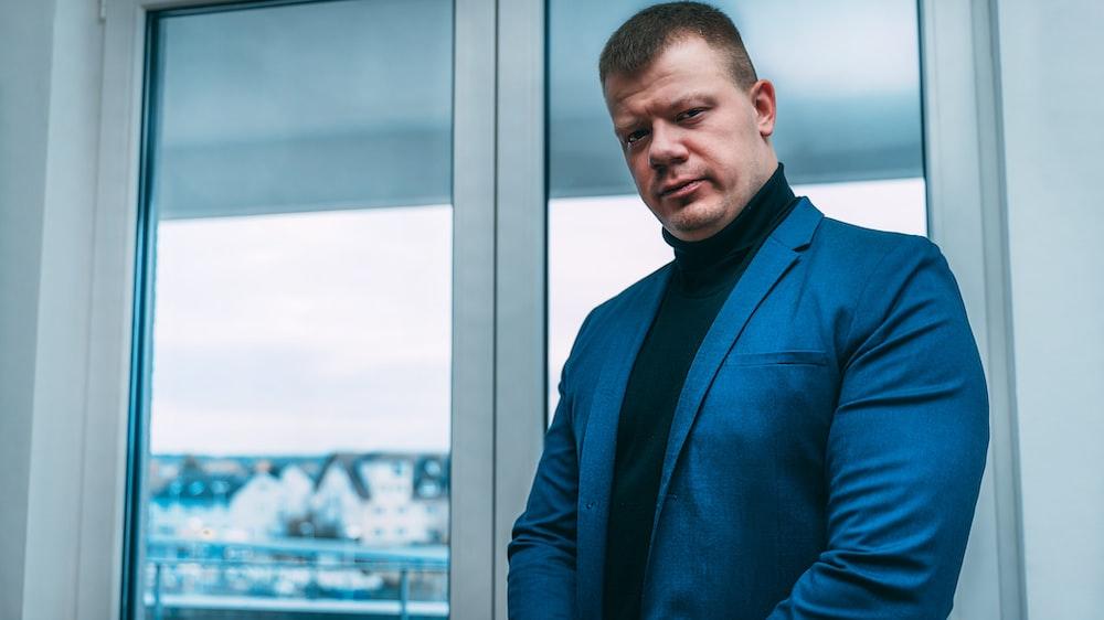 man in blue suit jacket standing beside glass window