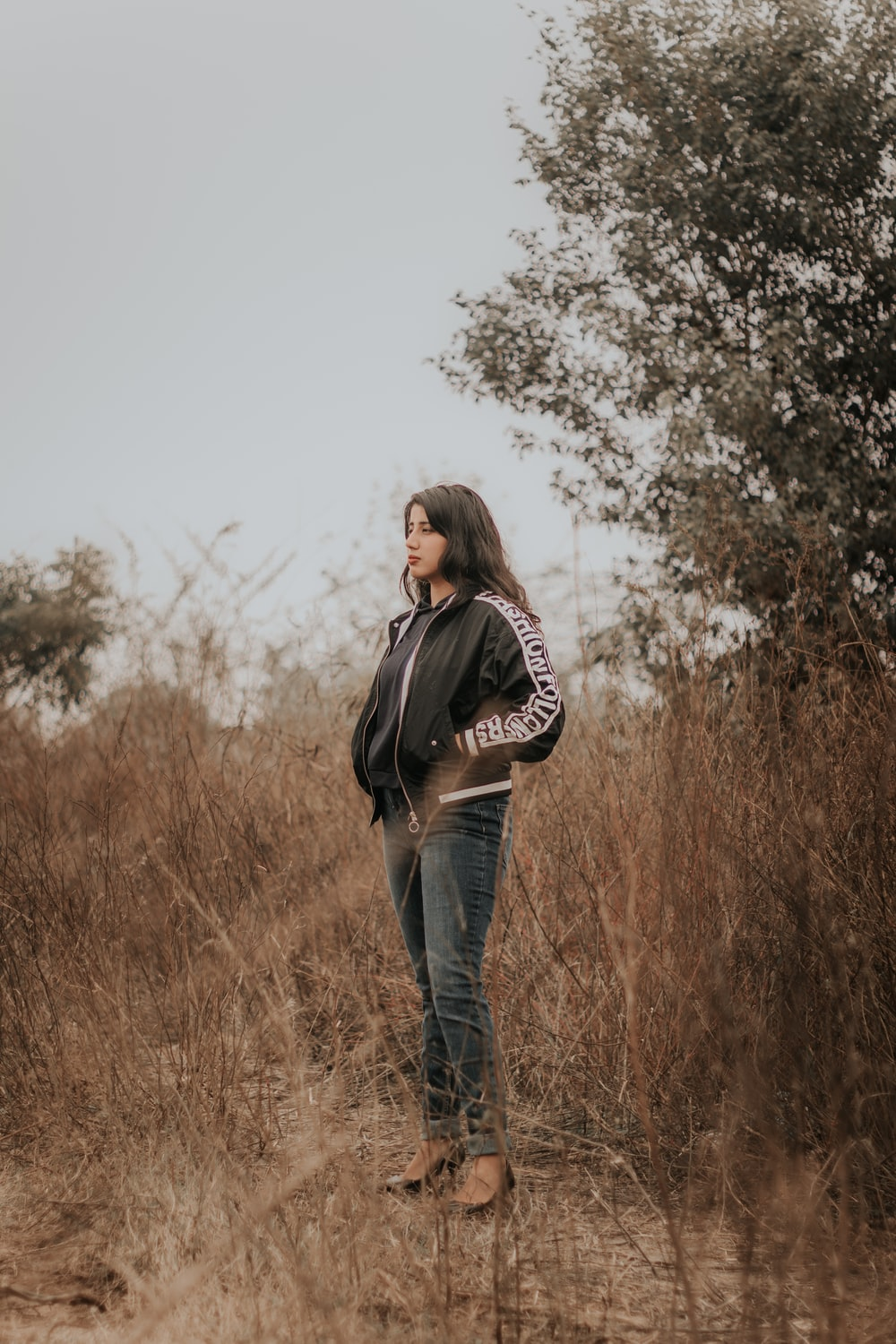 woman in black jacket and blue denim jeans standing on brown grass field during daytime