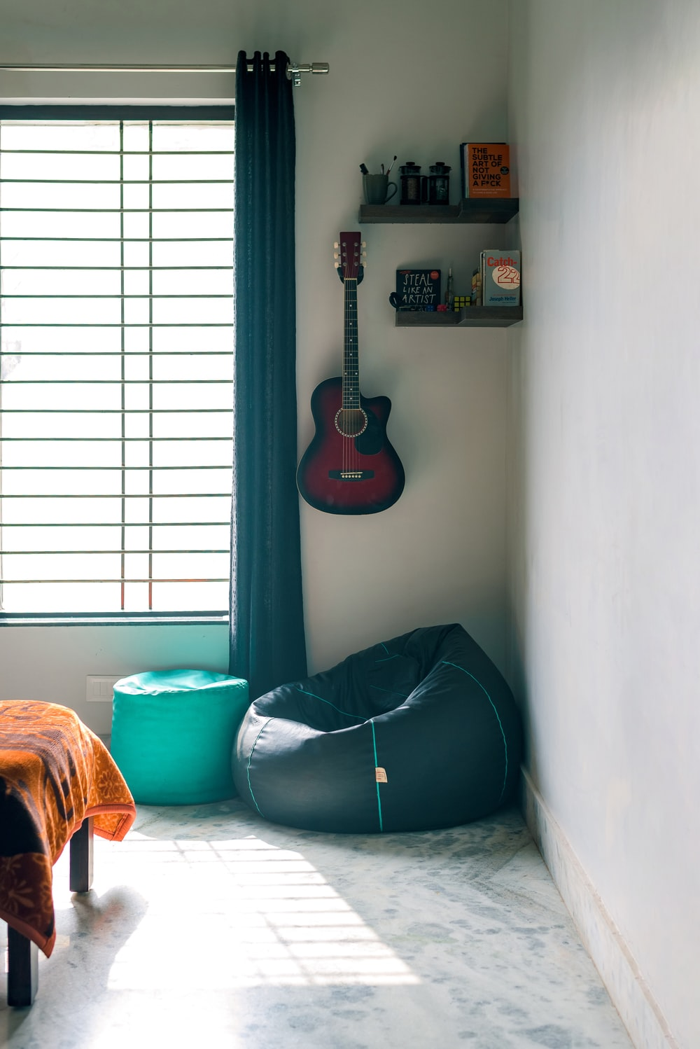 black and brown acoustic guitar on white wall