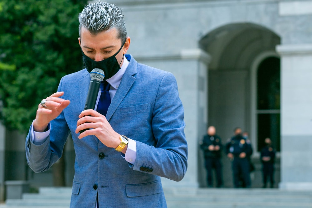 man in blue suit jacket holding black microphone