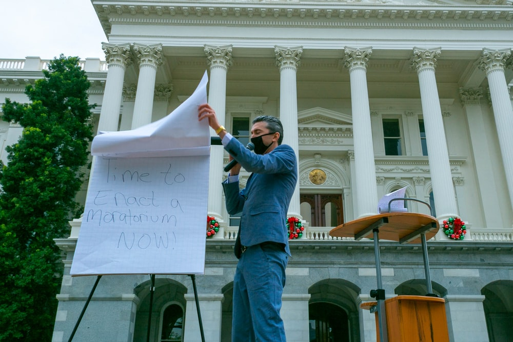 man in blue denim jacket holding white printer paper