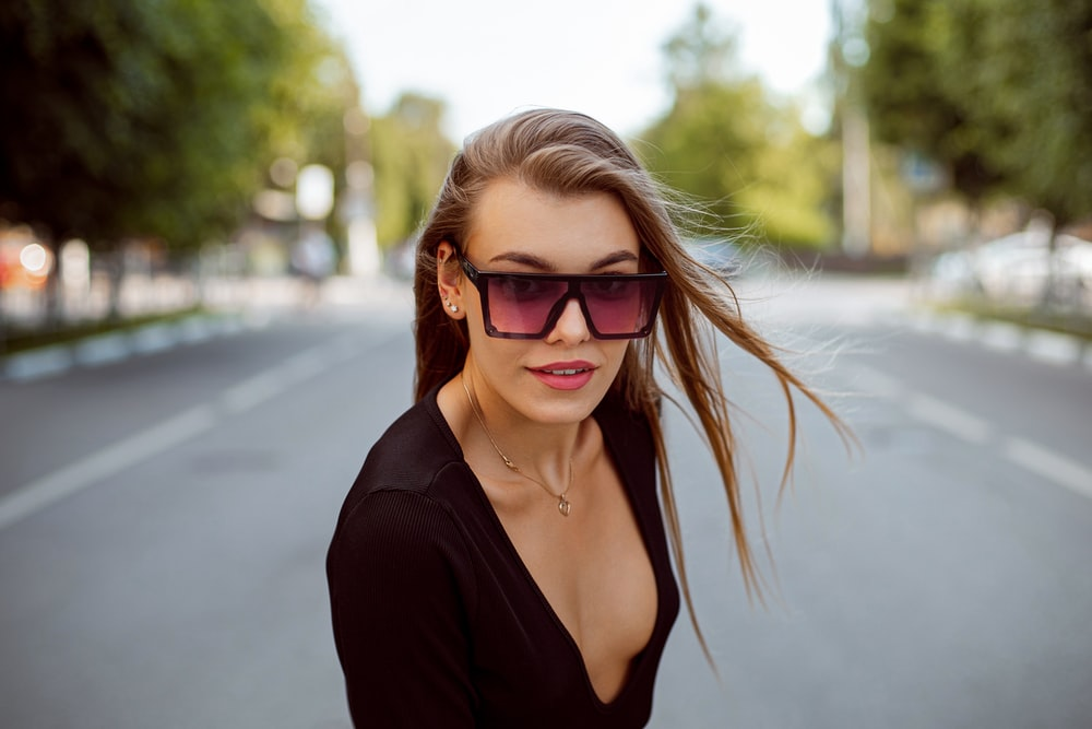 woman in black v neck shirt wearing brown sunglasses