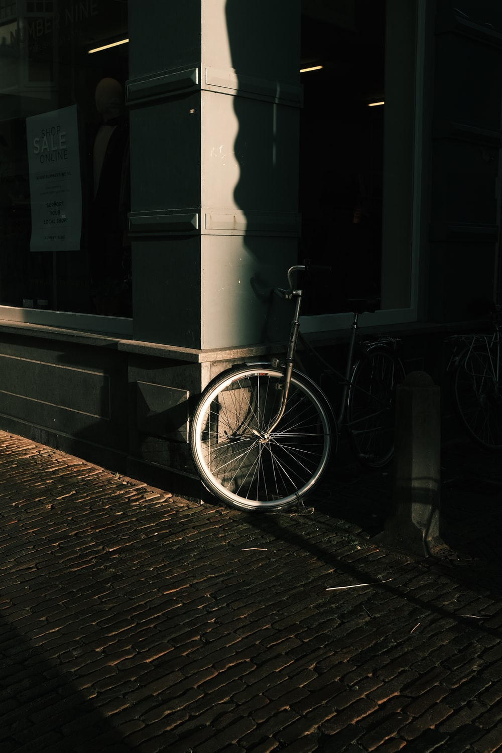 white bicycle parked beside brown brick wall