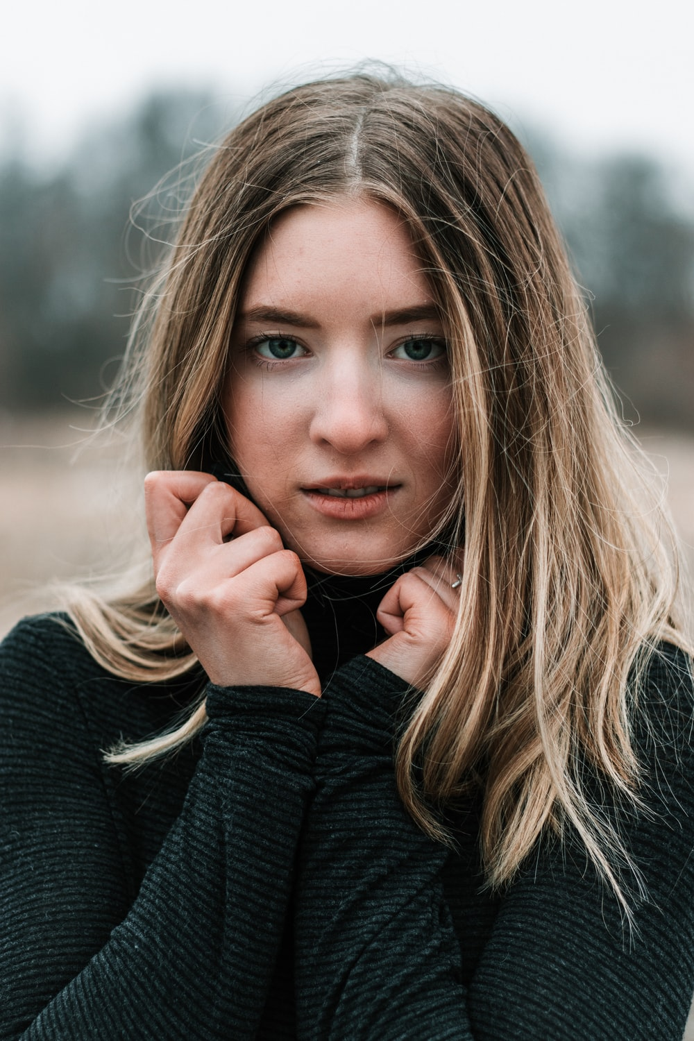 woman in black sweater holding her face