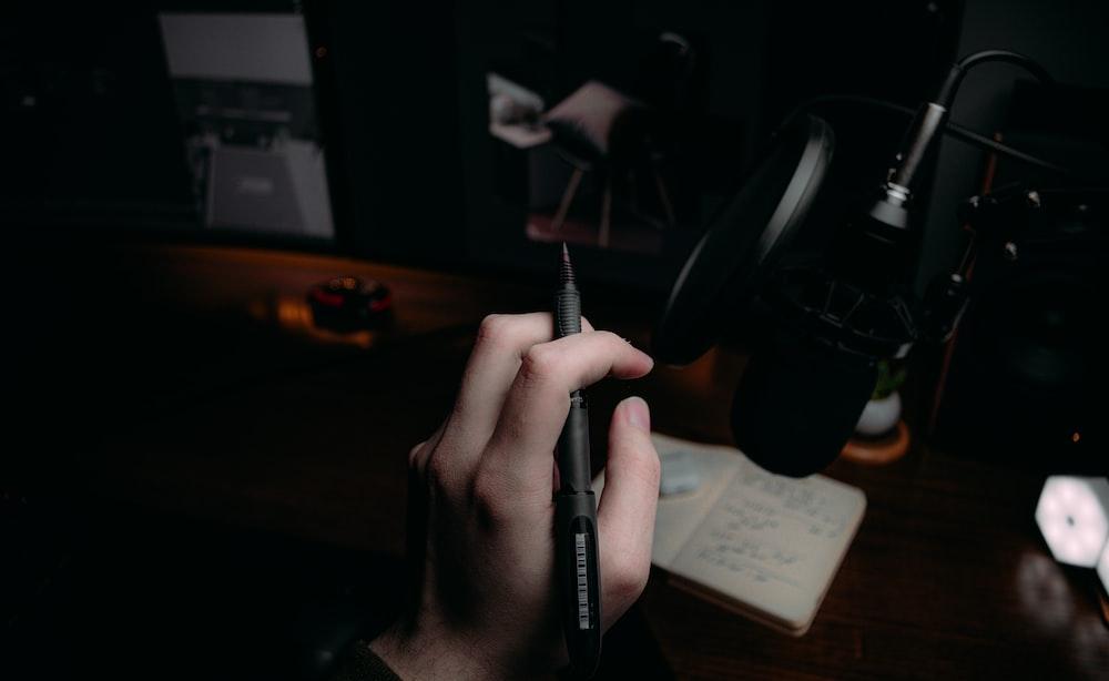 person holding black click pen