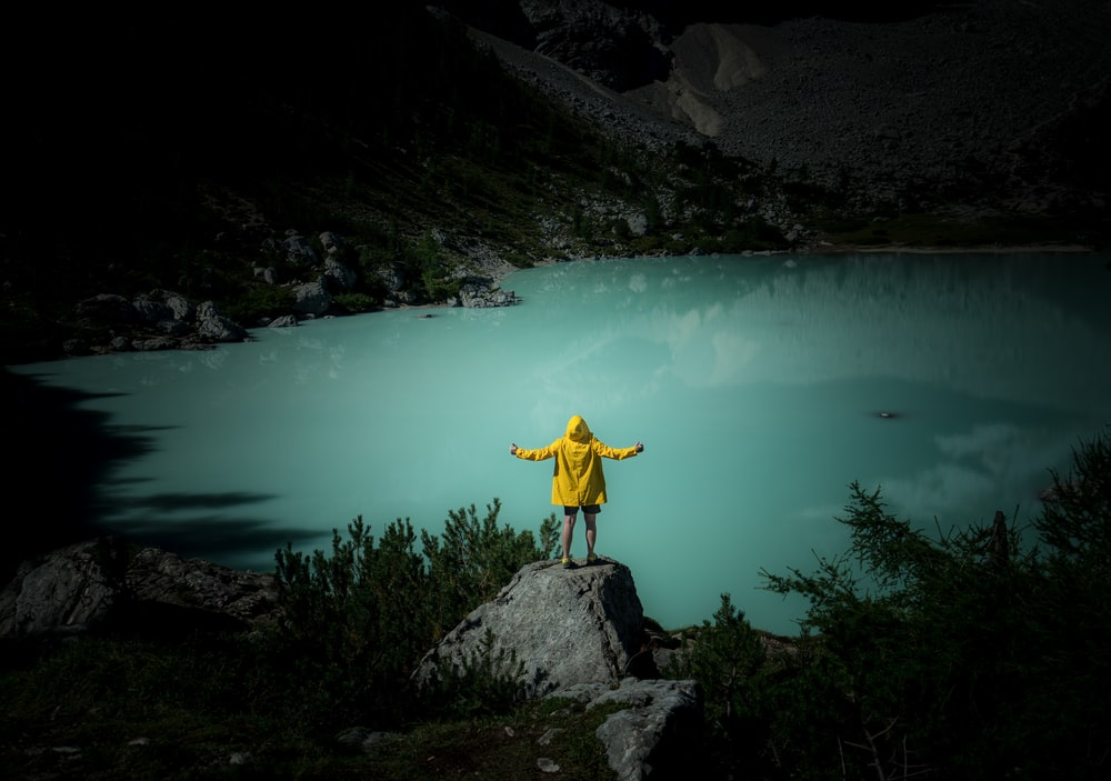 man in yellow jacket and blue denim jeans standing on rock near body of water during