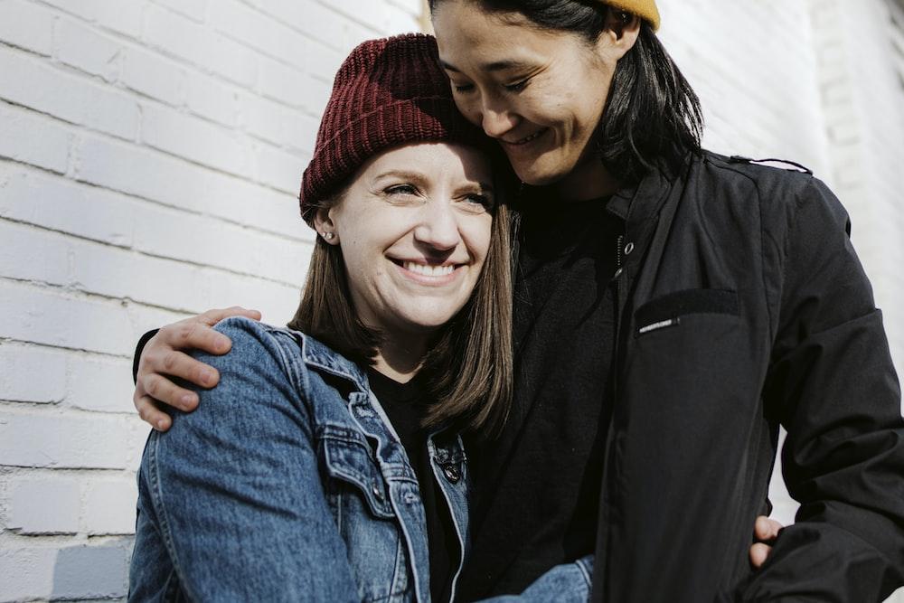 man in black jacket beside woman in blue denim jacket