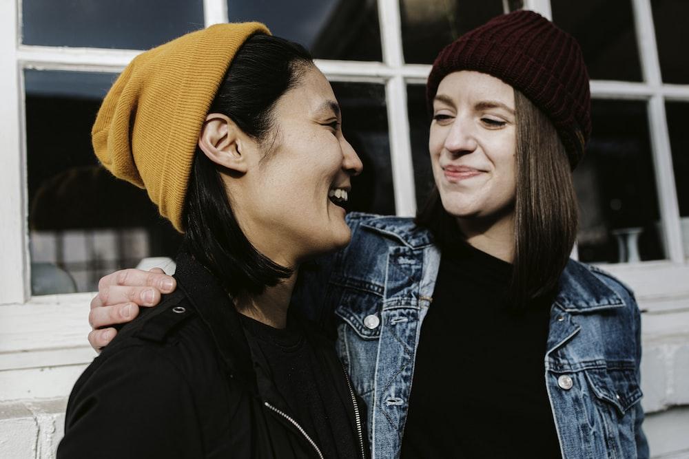 woman in black jacket beside woman in blue denim jacket