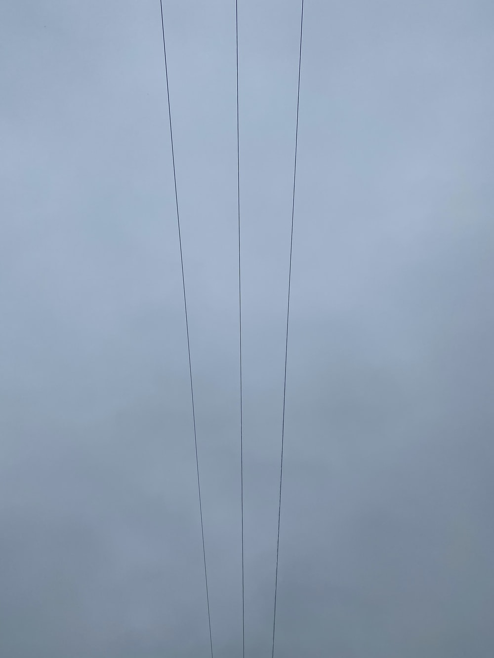 black coated wire under gray clouds