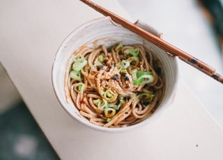 white ceramic bowl with noodles and chopsticks