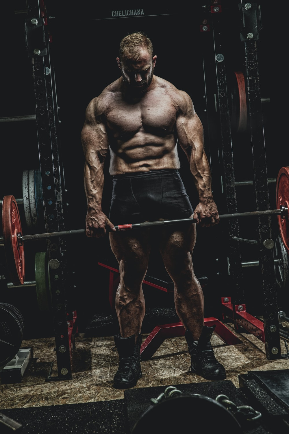 topless man in black shorts standing on black and red exercise equipment