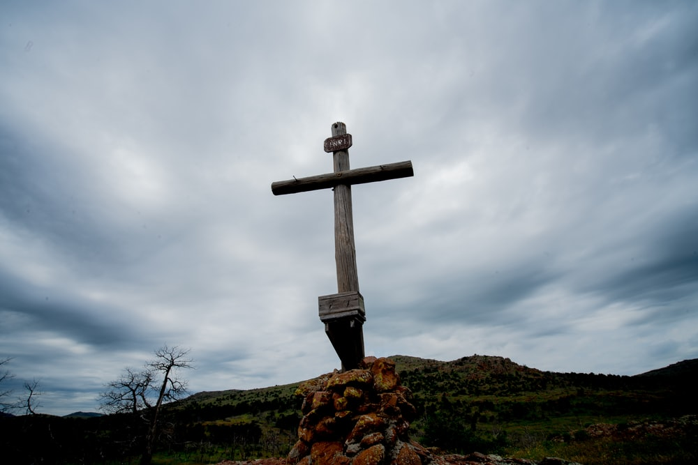 brown wooden cross on brown rock under white clouds during daytime