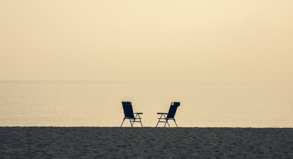 two black and white folding chairs on beach during daytime