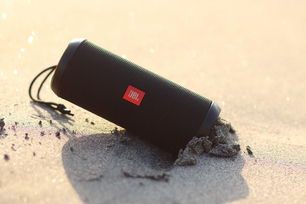 black jbl portable speaker on white and black textile