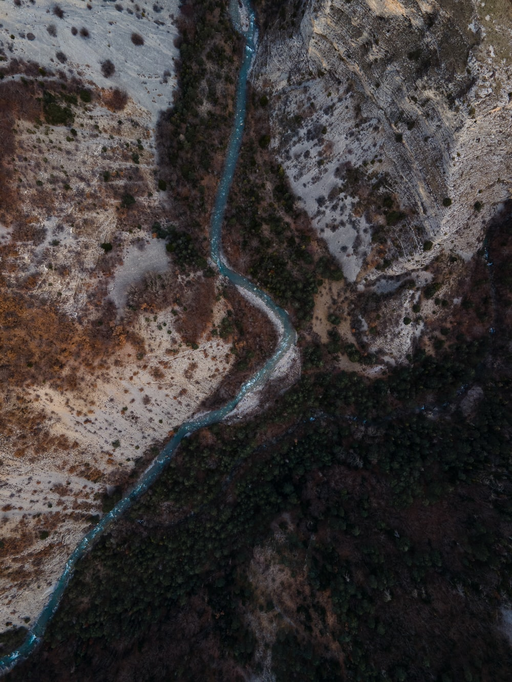 aerial view of road in the middle of brown rocky mountain