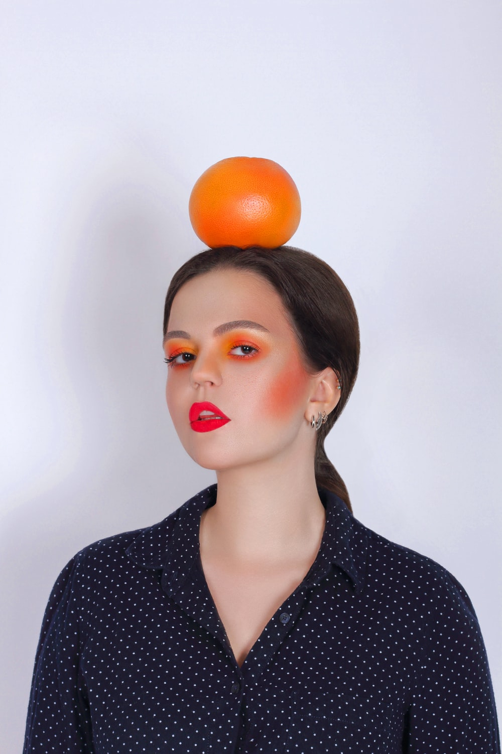 woman in black and white polka dot shirt with orange round fruit on her head