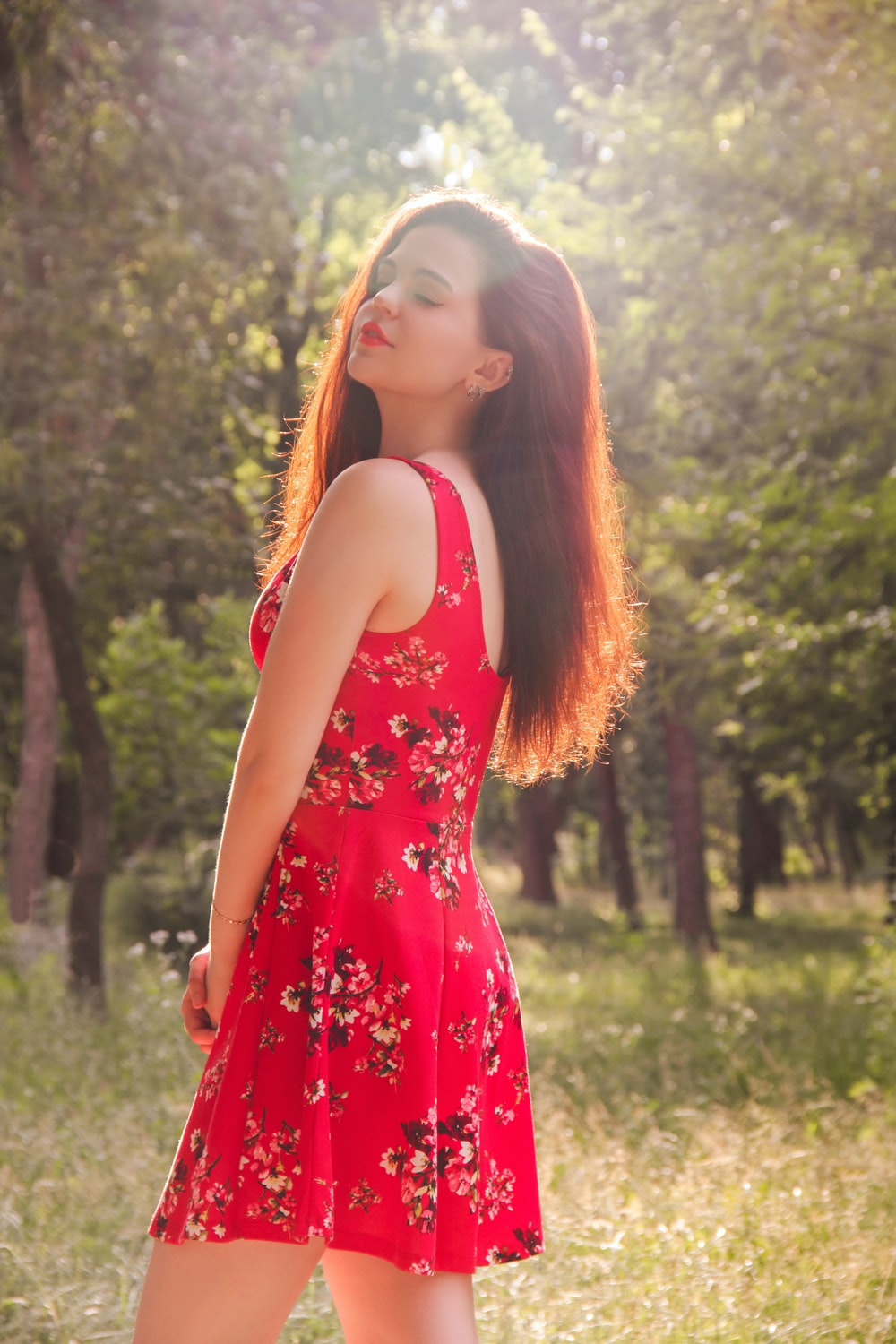 woman in red floral dress standing on green grass field during daytime