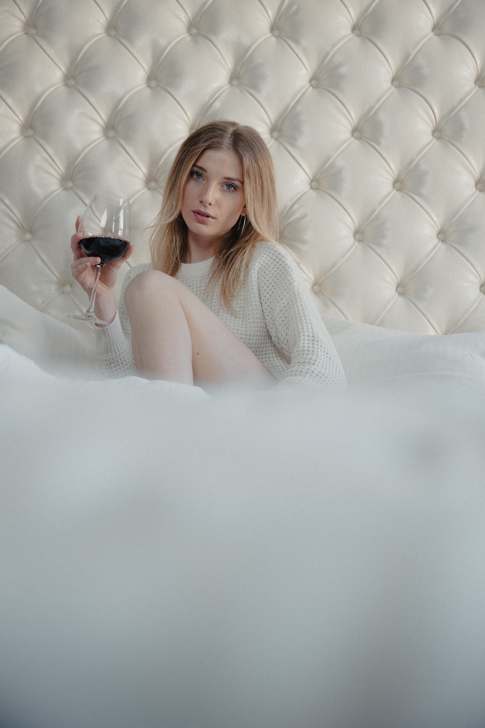 woman in white knit tank top lying on white bed
