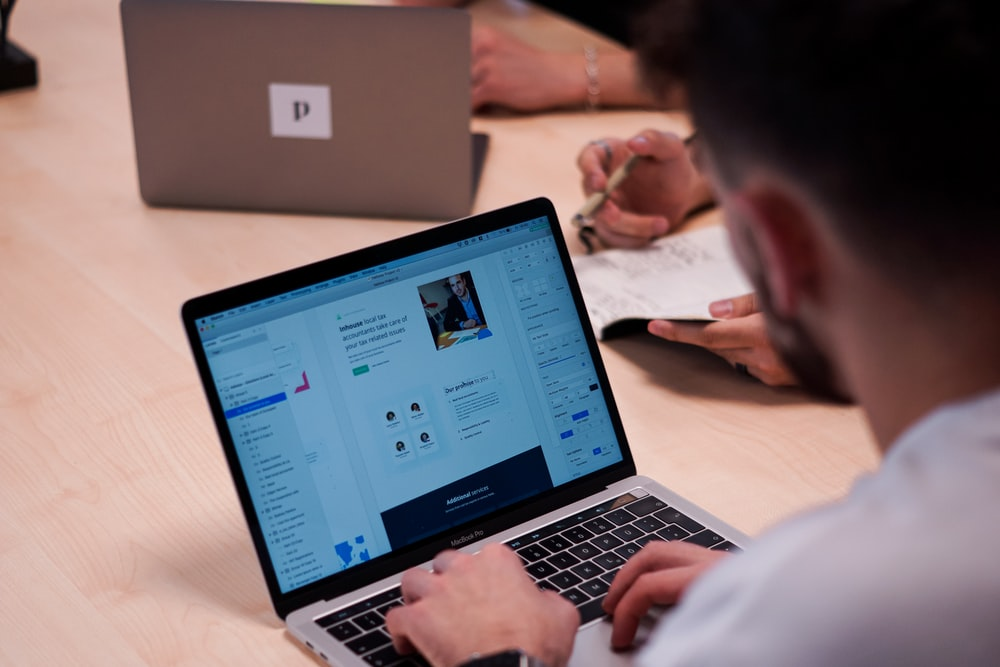 person using macbook pro on table