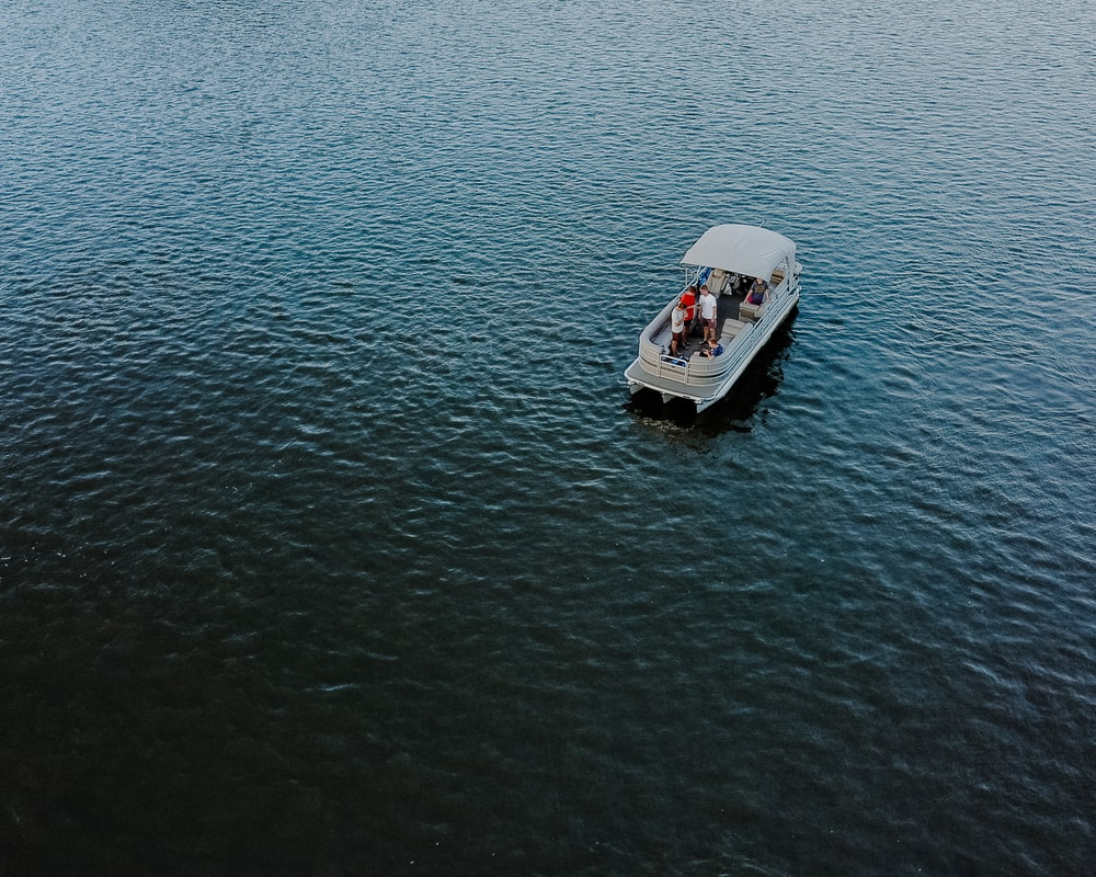 white and black boat on body of water during daytime