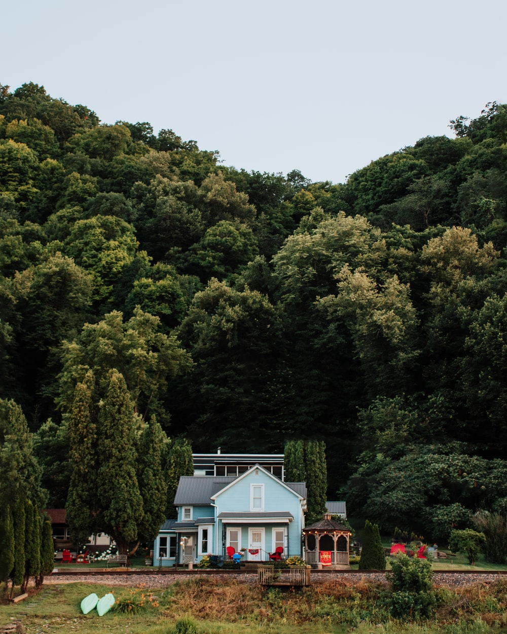 green trees near white and blue house during daytime