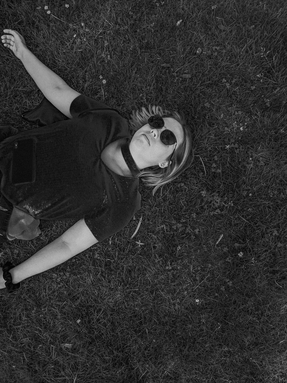 woman in black t-shirt lying on grass field