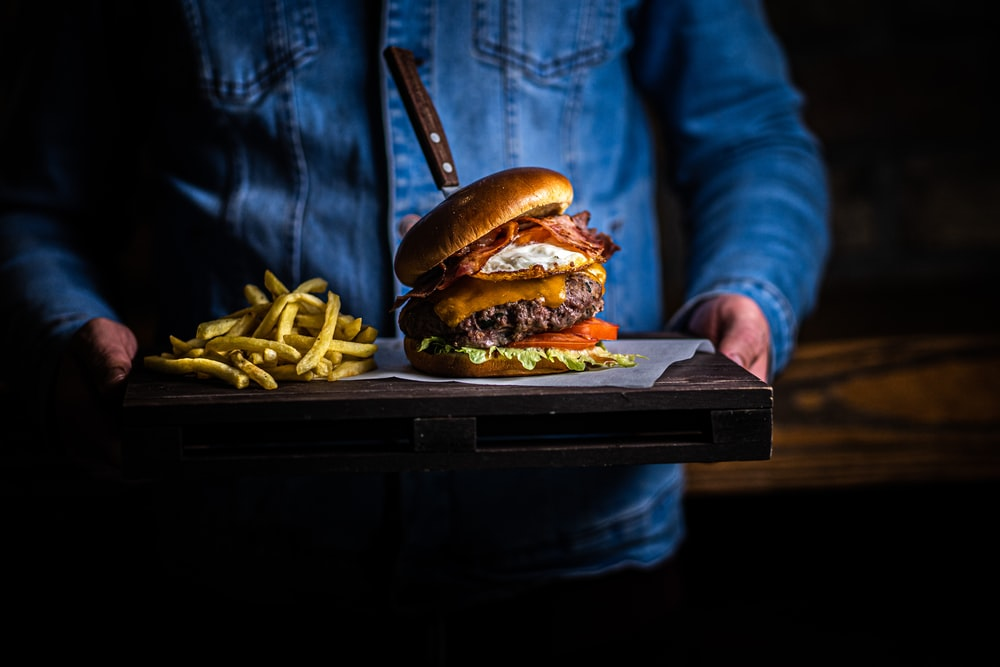 burger with fries on black tray