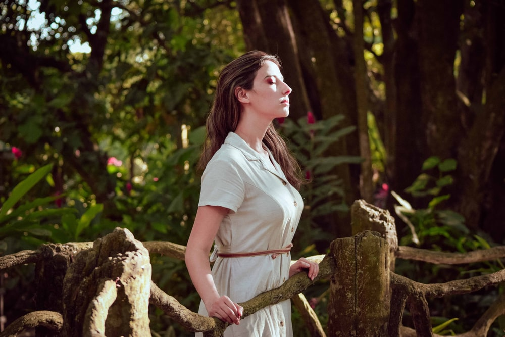 woman in white t-shirt and brown pants sitting on brown tree branch during daytime