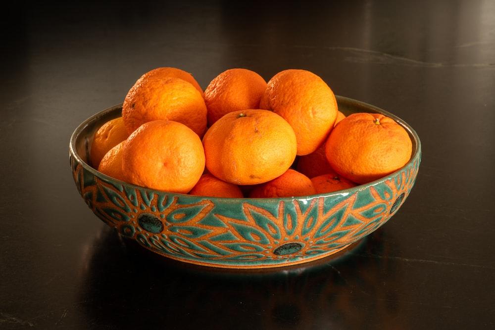 orange fruits on blue and white ceramic bowl