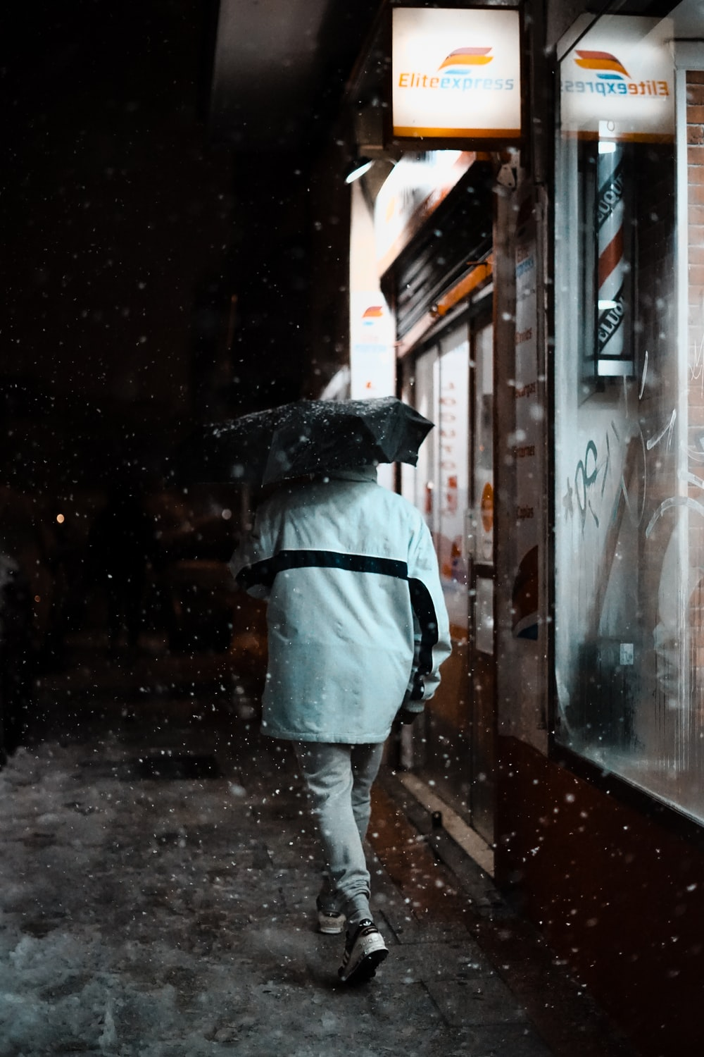 person in white shirt and gray pants with black umbrella standing on sidewalk during night time