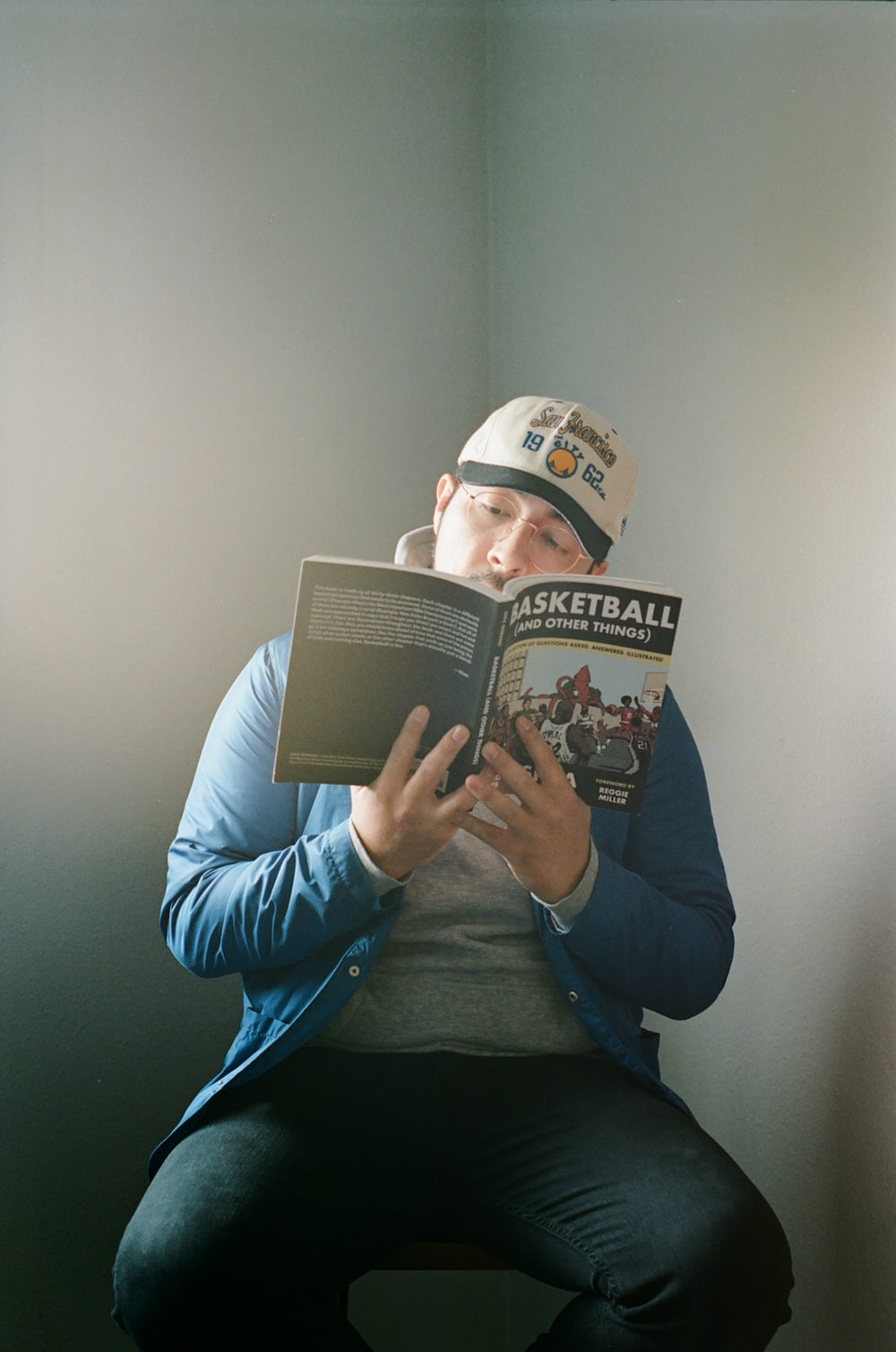 man in blue jacket reading book